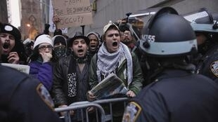 Occupy Wall Street protesters shout slogans to police officers while they march to the New York Stock Exchange