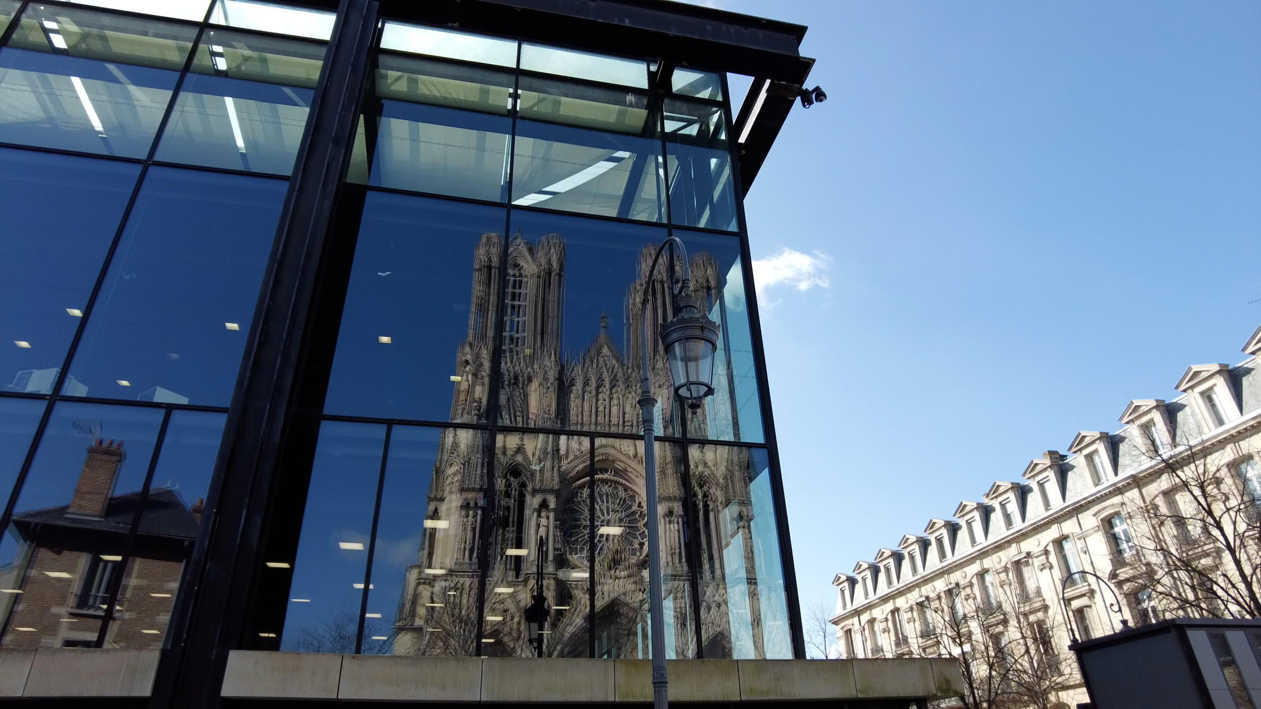 The city of Reims with its famous cathedral reflected on a building facade.