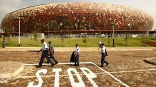 Des policiers patrouillant devant le Soccer City stadium de Johannesburg.
