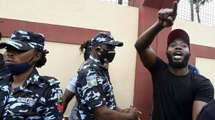 Mmoja wa waandamanaji wanaopinga ukatili wa polisi huko Ikeja akiandamana mbele ya maafisa wa polisi. Oktoba 9, 2020.