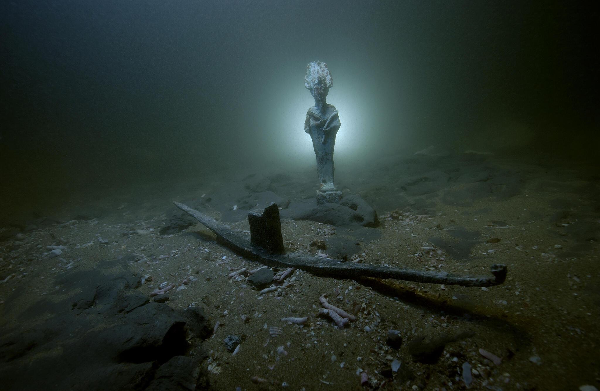 Statuette d'Osiris en bronze et barque votive en plomb posées sur les fonds sous-marin de la baie d'Aboukir. Thonis-Héracléion, Égypte, VIe - IIe s. av. J.-C.
