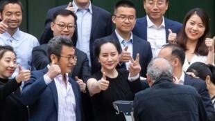 孟晚舟5月23日與包括華為副總裁彭博在內的多名支持者在加拿大一法院前豎起大拇指合照。