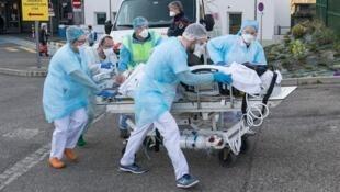 کادر پزشکی بیماری را بروی برانکارد بسوی بالگردی که باید او را به یک بیمارستان ویژۀ در شرق فرانسه منتقل کند، هدایت می کنند – ١٧ مارس ٢٠٢٠