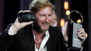 """O ator Paxton Winters recebe o prêmio Concha de Ouro para o longa brasileiro """"Pacificado"""", em San Sebastián."""