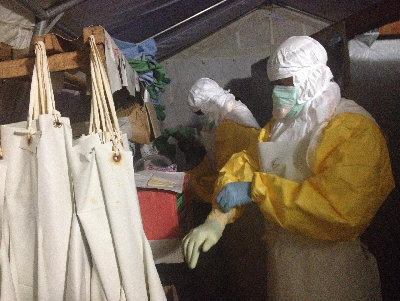 Des personnes s'équipent pour se protéger au maximum du virus Ebola dans le centre de traitement de Lokolia, en RDC