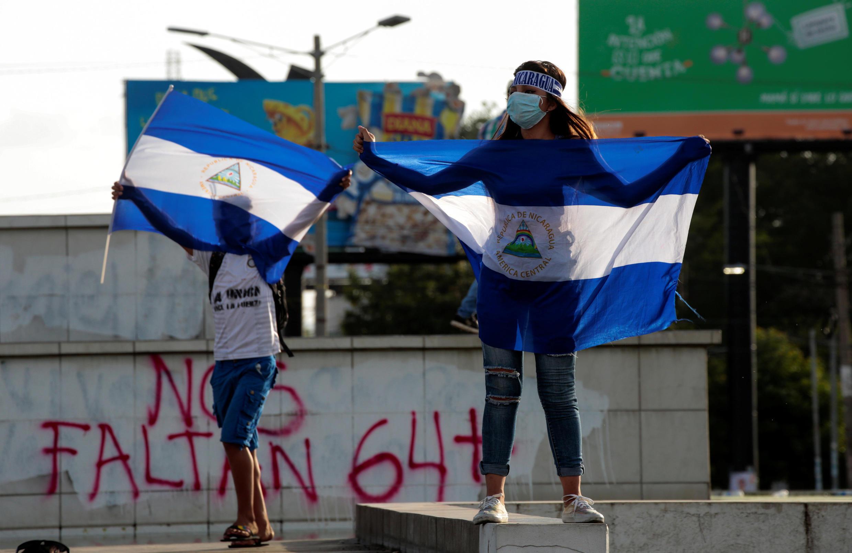 Des manifestants brandissent des drapeaux nicaraguayens en soutien à des adolescents tués lors des protestations contre Ortega.