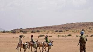 Un soldat de la Minuad et des civils, dans une région du Darfour, en juillet 2008.