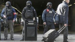 Des policiers montent la garde devant une station de train après les attentats qui ont touché la capitale belge, mardi 22 mars.