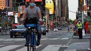 A person wearing a facemask and gloves bikes through Times Square on May 27, 2020 in New York City, amid the novel coronavirus pandemic