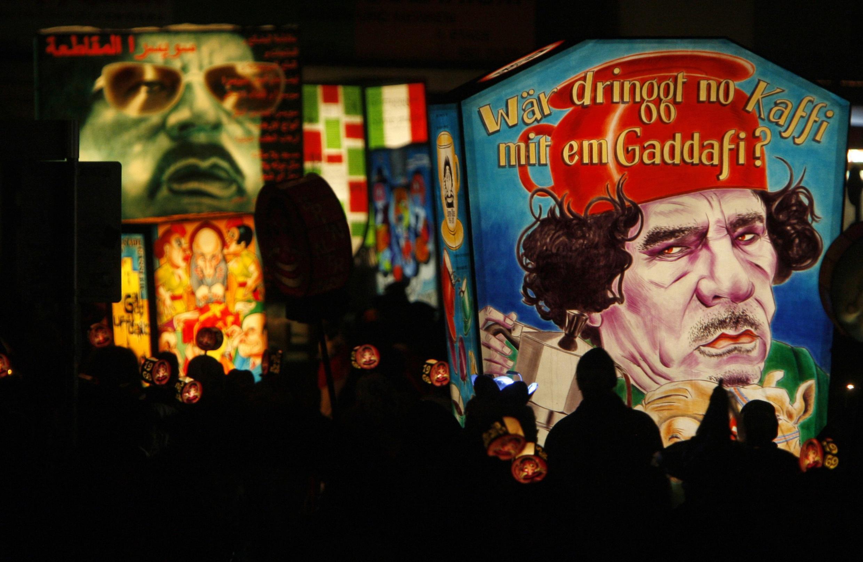 Revelers carry representations of Libyan leader Moamer Kadhafi, 22 February 2010