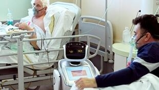 Un patient interagit avec un robot qui aide les équipes médicales à traiter les patients atteints de la maladie Covid-19 à l'hôpital Circolo, à Varese,  en Italie, le 1er avril 2020.