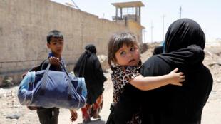 Des civils fuient le quartier de Zanjali, à Mossoul, le 7 juin 2017.