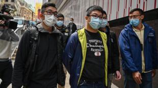 Ben Chung (C) de un grupo político prodemocracia es arrestado por la policía en Hong Kong, el 6 de enero de 2021, bajo una nueva ley de seguridad nacional impuesta por Pekín