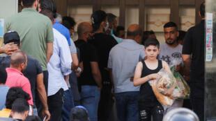 Des Libanais font la queue devant une boulangerie pour se ravitailler en pain, le 27 juin 2020.