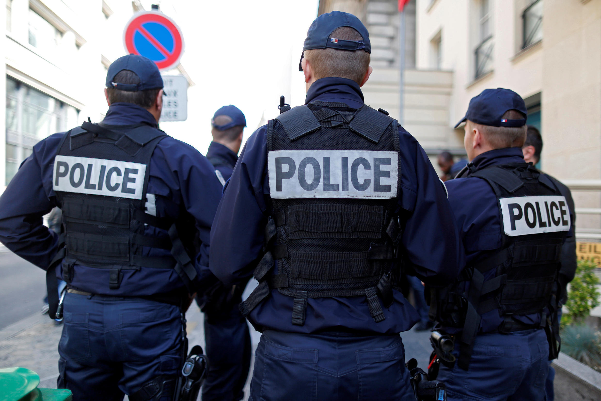 French police gather outside a local police station in Paris after the Molotov cocktail attack