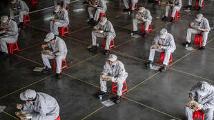 Empleados de una fábrica de automóviles comen durante la pausa para almorzar guardando la distancia de seguridad por la pandemia del coronavirus, el 23 de marzo de 2020 en la ciudad china de Wuhan