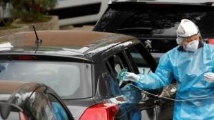 Un empleado del Hospital Cotugno de Nápoles, Nápoles, provee de oxígeno a un paciente  en su coche por falta de espacio, 12 de noviembre de 2020.