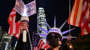 A participant holds a torch and wears headgear modelled after the Statue of Liberty as people assemble for a gathering of thanks at Edinburgh Place in Hong Kong's Central district on November 28, 2019