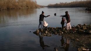 Des migrants se tiennent sur les bords de la rive Evros, la frontière naturelle entre la Grèce et la Turquie, près de la ville turque d'Edirne, le 3 mars 2020.