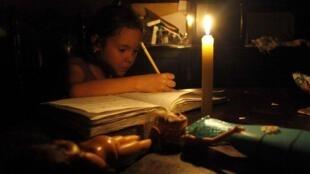 Una niña hace sus tareas a la luz de una vela durante un corte de electricidad en San Cristóbal, estado Táchira, el 25 de abril de 2016.