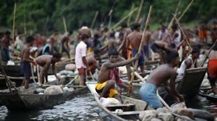 Công nhân thu nhặt đá trên dòng sông Piyain tại Jaflong, Silhet, Ấn Độ. Hàng ngàn công nhân làm việc ở đây trong đó có cả phụ nữ và trẻ em, kiếm được khoảng 2,9 đô la một ngày.