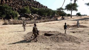 Village sur le flanc des monts Nuba. Des enfants passent à coté des trous. «Là, vous voyez le trou là? c'est une bombe. L'autre est dans l'enceinte dans la mosquée.»