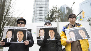 Protesters hold photos of Canadians Michael Spavor and Michael Kovrig in Vancouver in March 2019. The pair have now been detained in China for nearly two years and face charges of spying