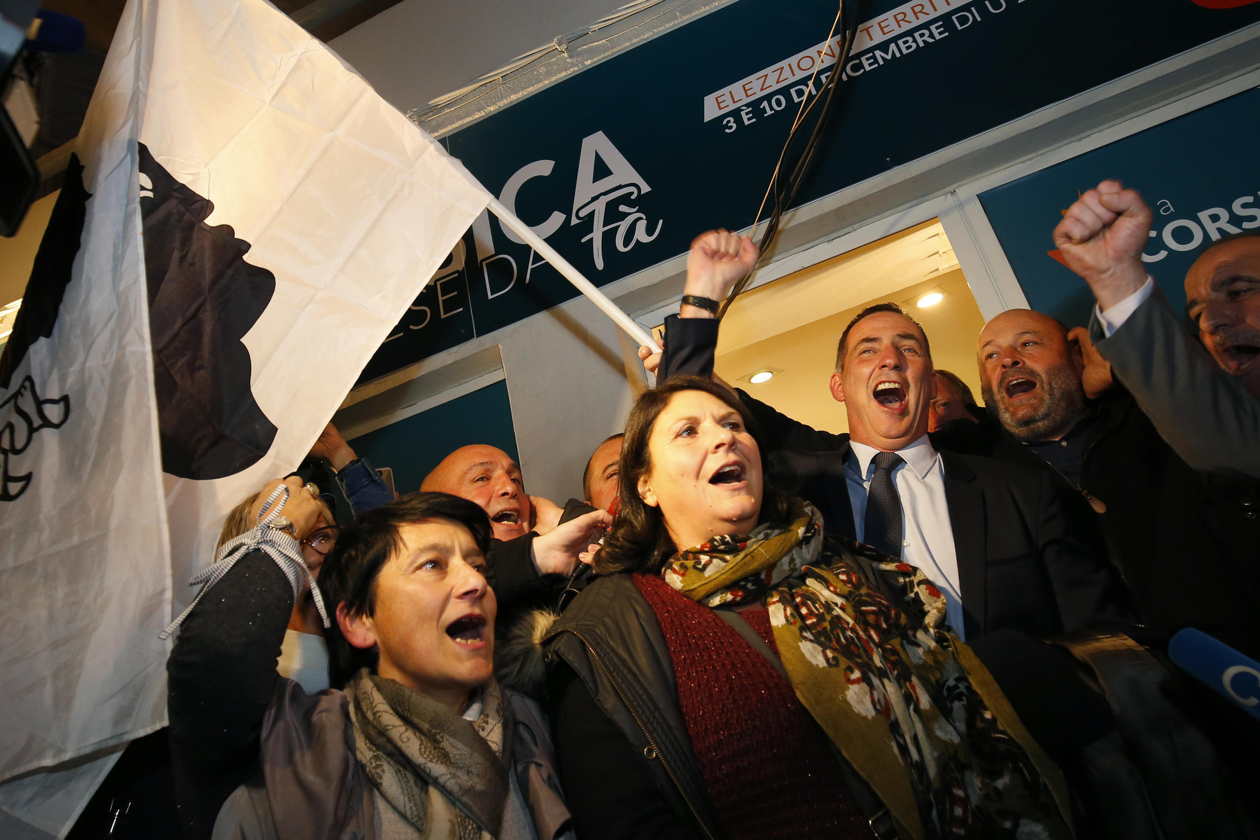 Gilles Simeoni (C) and other Corsican nationalists celebrate Sunday's result