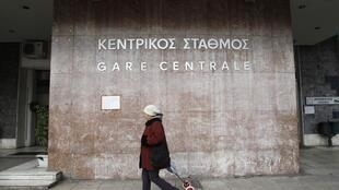 A woman walks outside a train station which ceased operation during a strike in Athens February 23, 2011.
