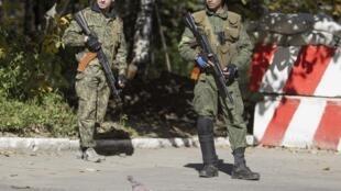 Rebelles pro-russes installés à un check-point sur une route, près de Donetsk, le 3 octobre.