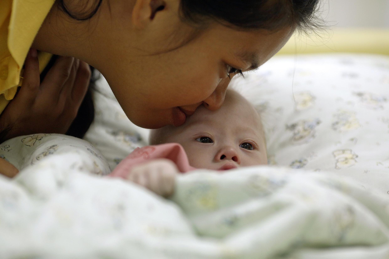 Le petit Gammy, en compagnie de sa mère porteuse, le 3 août 2014 à l'hôpital, dans la province thaïlandaise de Chonburi.