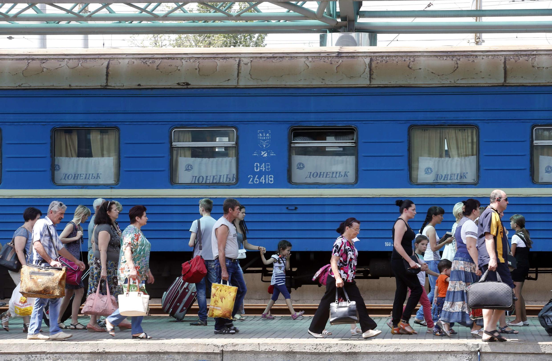 Passageiros caminham ao longo de plataforma na estação ferroviária de Donetsk; muitos habitantes estão partindo da cidade neste final de semana por medo de um ataque do exército.