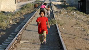 A girl walks along a broken railway track in the rebel-held al-Sheikh Said neighbourhood of Aleppo, Syria September 1, 2016