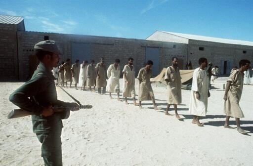 Dans un camp militaire à quelques km de Nouakchott, un soldat mauritanien surveille des prisonniers du Front Polisario (17 novembre 1977).