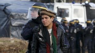 Un policía detiene a un joven afgano en el campamento de Calais, 29 de febrero de 2016.