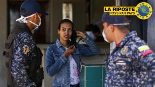 Des membres de la police nationale bolivarienne demandent à une femme de mettre un masque par mesure de précaution contre la propagation du nouveau coronavirus à Caracas, le 16 mars 2020
