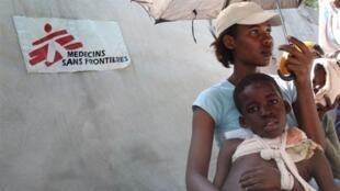 Une femme et son enfant blessé patientent devant la tente MSF de Port-au-Prince, le 16 janvier 2010.