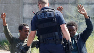 A police officer with migrants in Calais