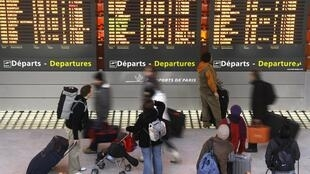 Passengers check flight information board at Paris Charles de Gaulle airport