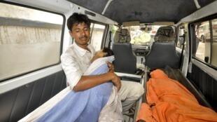 Отец в машине скорой помощи со своим ребенком, получившим отравление школьным обедом в г. Патна 17/07/2013