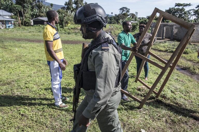 Un gendarme passe devant des officiels en train d'installer un bureau de vote à Mwangai près de Buea en zone anglophone.