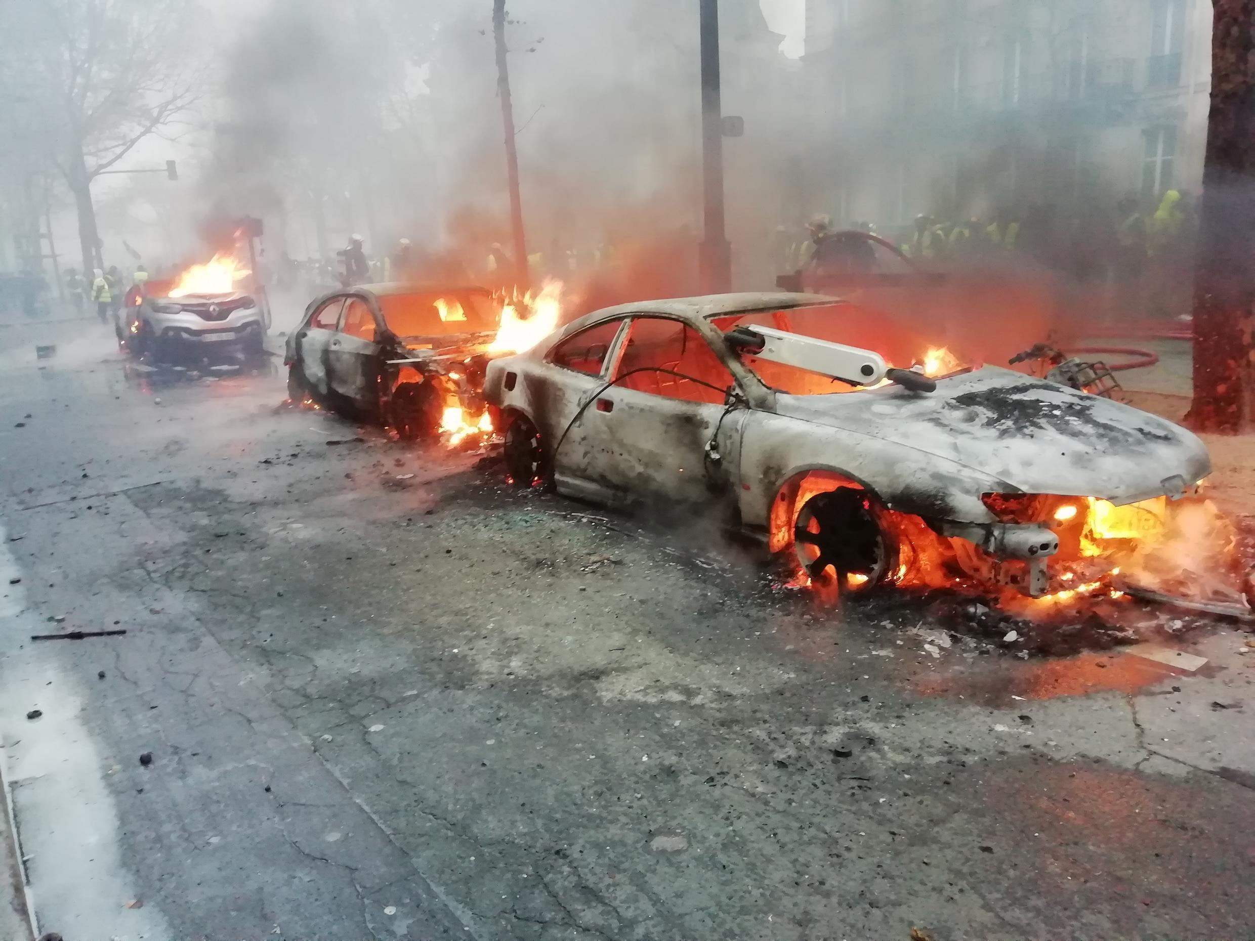 Firefighters arrive to extinguish three torched cars.