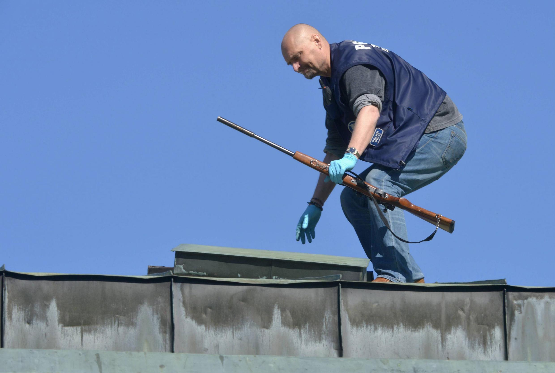 Policial recolhe espingarda do telhado de onde atirador matou dois jovens.