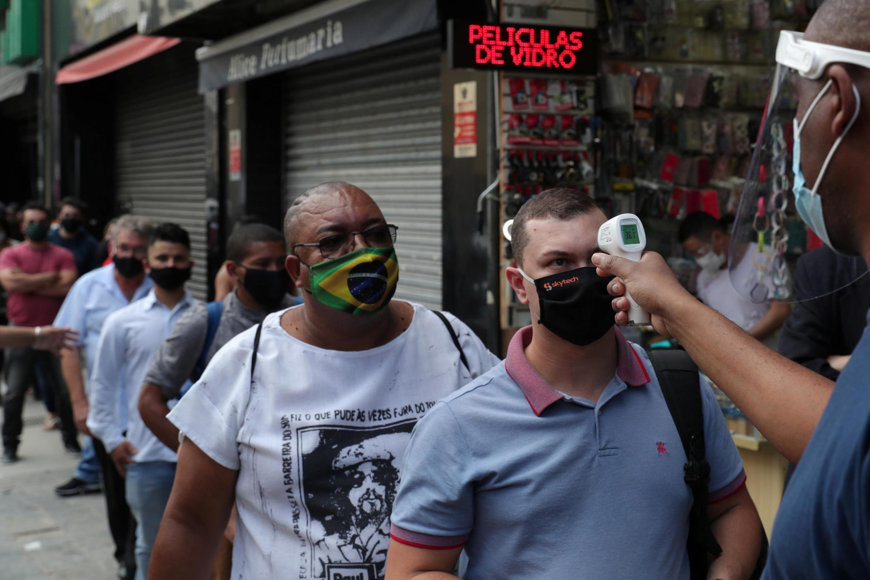 Prise de température avant l'accès aux grandes surfaces, les «malls», qui ont rouvert à Sao Paulo, au Brésil, le 11 juin 2020, malgré les chiffres alarmants de contamination au Covid-19.