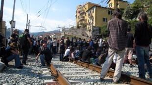 Une soixantaine de migrants tunisiens et un groupe de militants français et italiens manifestent sur les voies de la gare de la ville frontière italienne de Vintimille, le 17 avril 2011.