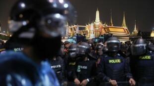 Les policiers thaïlandais forment un cordon de sécurité pour empêcher les manifestants d'atteindre le Grand Palais, à Bangkok, lors d'une manifestation anti-gouvernementale, le 8 novembre 2020.