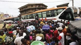 A la gare routière d'Adjamé, des familles fuyant la violence, espèrent monter dans les bus pris d'assaut, à Abidjan, le 20 mars 2011.