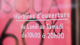 Placa indica os horários de abertura da loja.