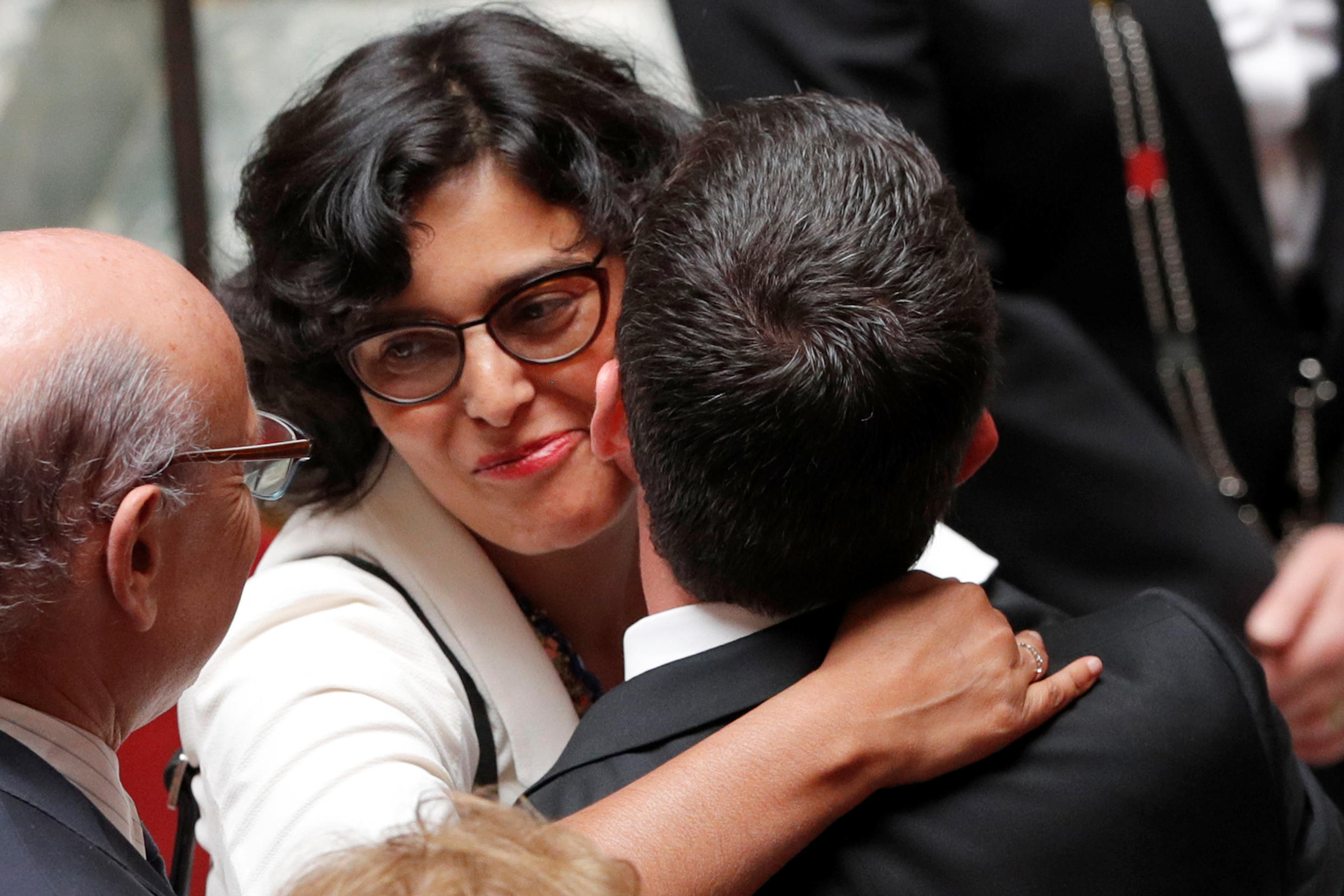 French Prime Minister Manuel Valls (R) kisses Labour Minister Myriam El Khomri (C) after forcing the labour law through parliament