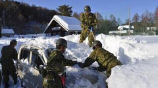 Des forces de sécurité japonaises déblaient la neige sur une voiture, dans la préfecture de Yamanashi, à l'ouest de Tokyo, le 16 février 2014.